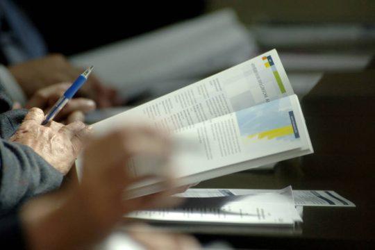 Hände halten eine offene Publikation und einen Kugelschreiber.