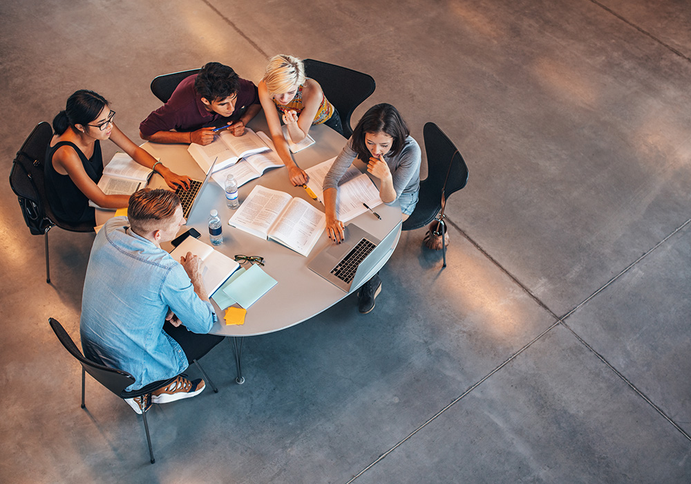 Studierende sitzen an einem Büchertisch und schauen auf einen Laptop.