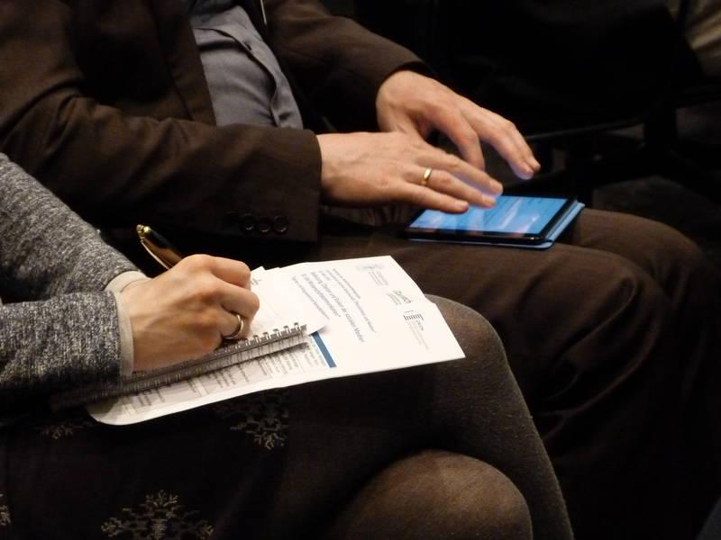 Zwei Handpaare benutzen einen Notizblock und ein Smartphone.