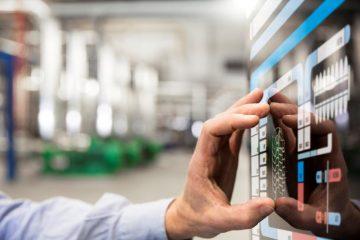 Eine Hand bedient ein Wandtablet in einer Fabrik.