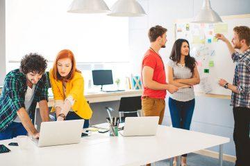 Zwei und drei Leute diskutieren an einem Laptop und einem Whiteboard.