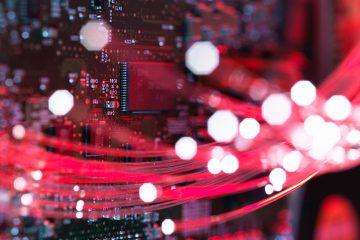 Rot leuchtende Glasfaserkabel vor einer Platine.