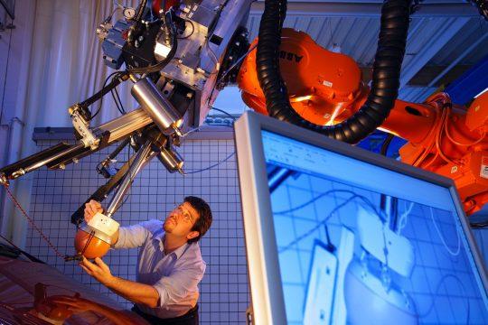 Ein Mann justiert einen Roboterarm in einem Labor.