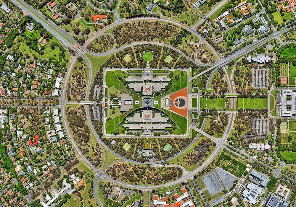 Industriegebäude, das von einem Ring aus Bäumen, Straßen und Gebäuden umgeben ist.