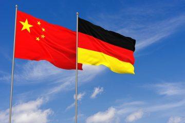 Chinesische und deutsche Flagge vor blauem Himmel