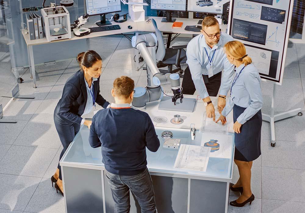 Wissenschaftlerinnen und Wissenschaftler diskutieren im technischen Labor.
