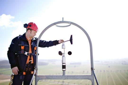 Ein Facharbeiter justiert ein Windmessgerät.