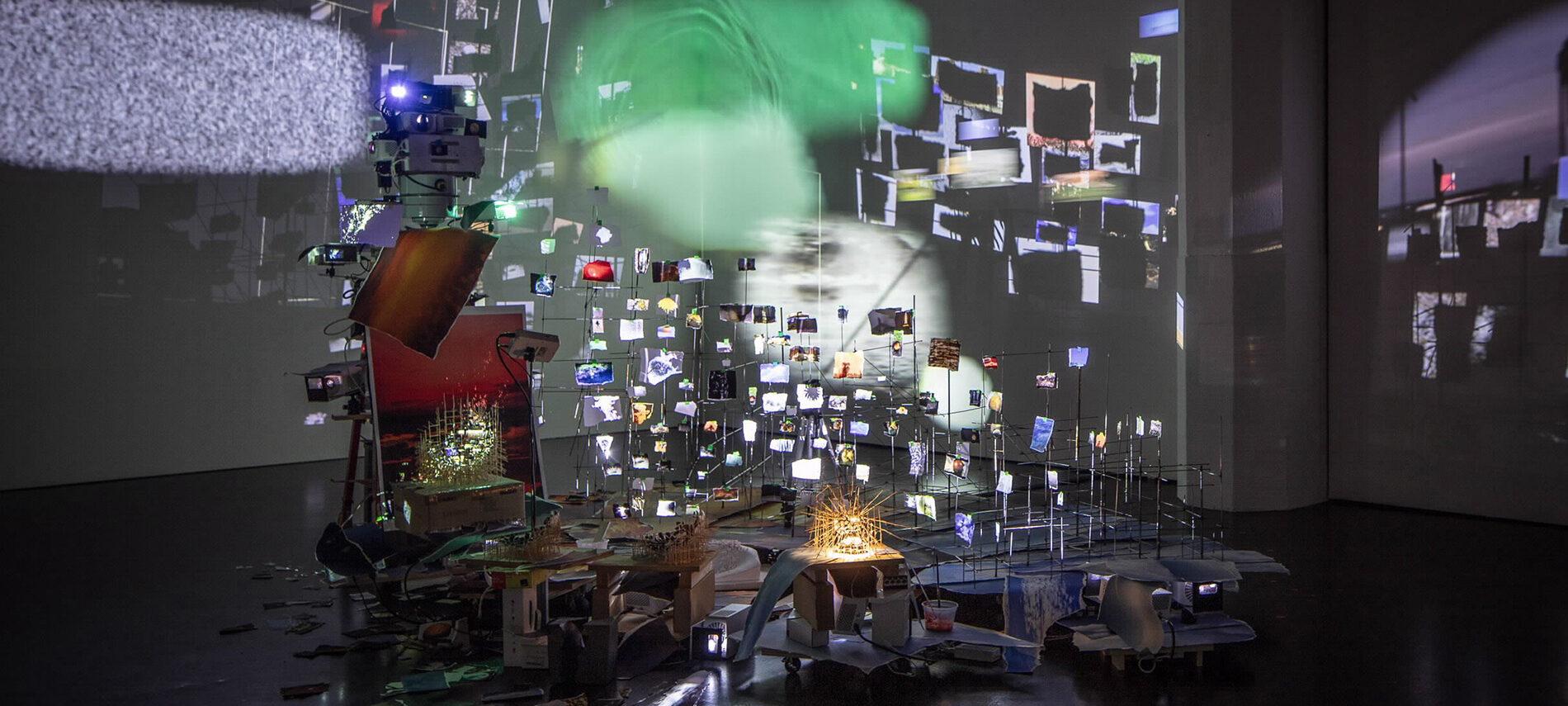 Bild einer Kunstinstallation in der Ausstellung Critical Zones mit Fotos und Licht