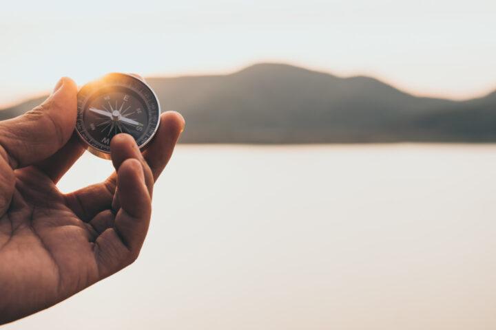 Foto Hand hält Kompass in die Luft