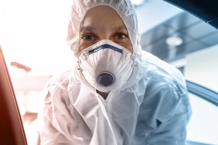 Medizinische Fachkraft im Schutzanzug während einer mobilen Covid-Testung