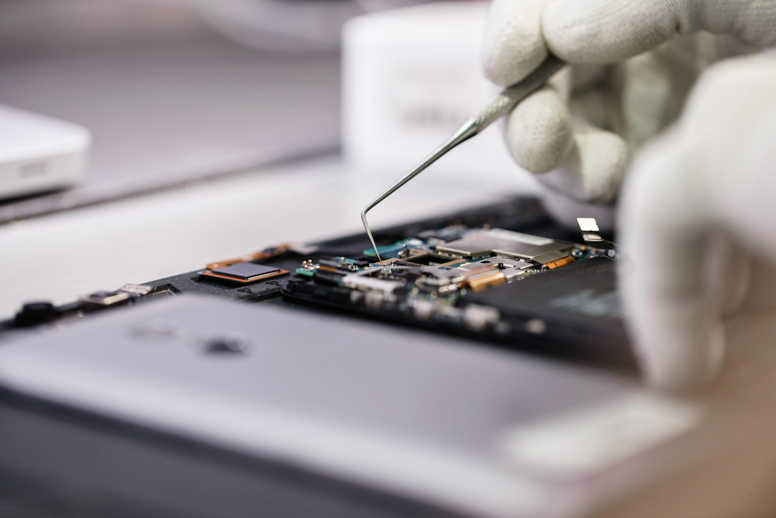 Nahaufnahme Hände eines Servicemitarbeiters, der ein modernes Smartphone repariert.