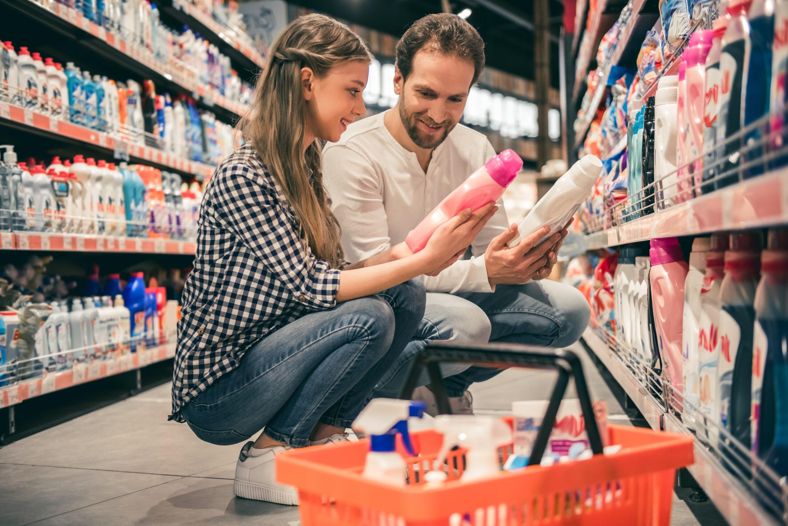 Eine Frau und ein Mann im Supermarkt. Sie halten jeweils eine Flasch Waschmittel aus Plastik in den Händen.
