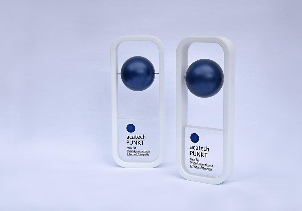 Zwei Pokale des Journalistenpreises. Weißer Rahmen mit blauer Kugel.