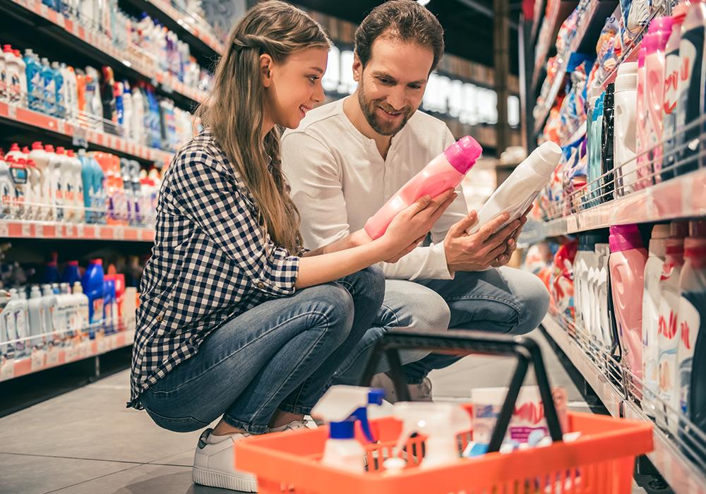 Zwei Personen im Supermarkt mit Waschmittel in der Hand