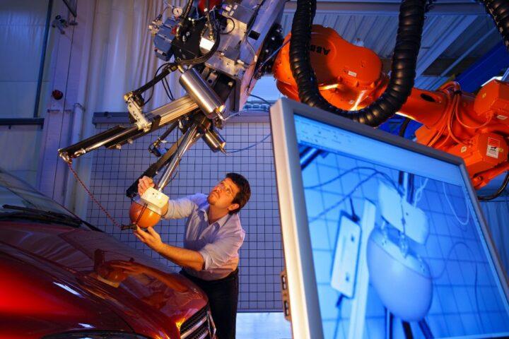 Foto Mann arbeitet mit einem technischen Gerät an einem Auto