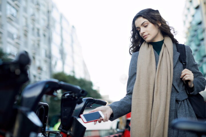 Frau hält Handy in der Hand und geht vorwärts