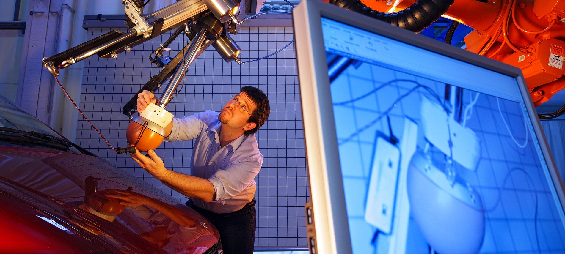 Foto Titelbild Publikation: Mann arbeitet mit einem technischen Gerät an einem Auto